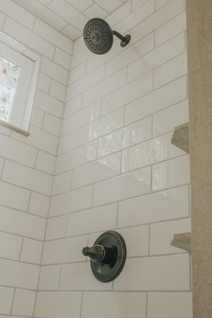 Before and After Mid Century Bathroom Renovation   White Subway Tile Shower and Bronze Hardware